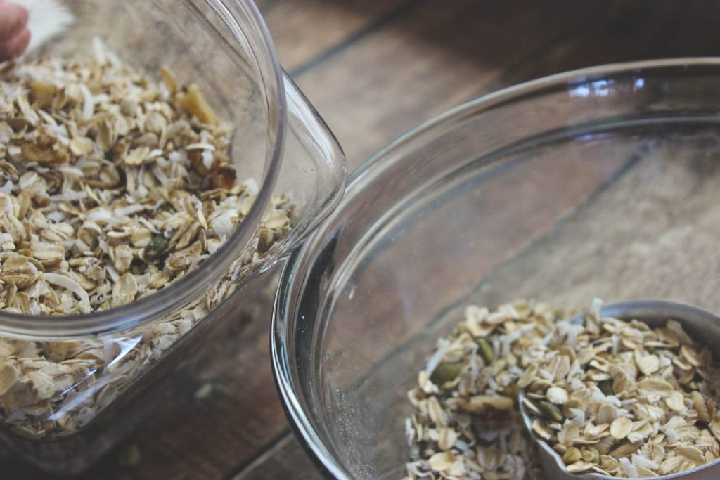 Adding muesli to an airtight container for storage.